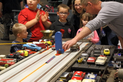 The grandchildren doing the slot car racing with the help of Mike Lowhorn